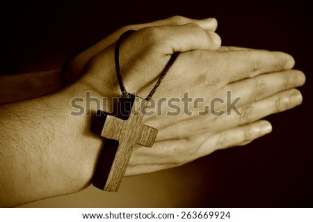 closeup of a young man praying with a wooden cross in his hands, in sepia toning - stock photo