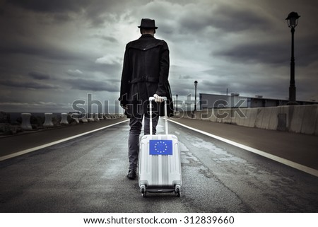 closeup of a young man seen from behind carrying his rolling suitcase with an European flag, with a dramatic effect - stock photo