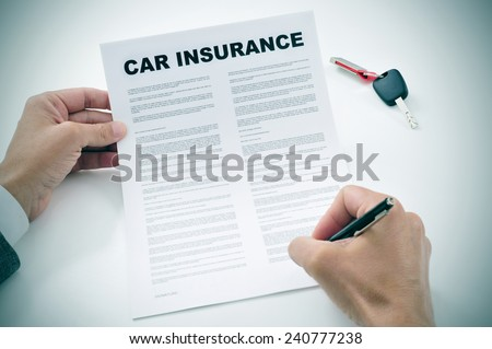 closeup of a young man signing a car insurance policy - stock photo