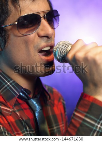 Closeup of a young man singing into microphone on stage at concert