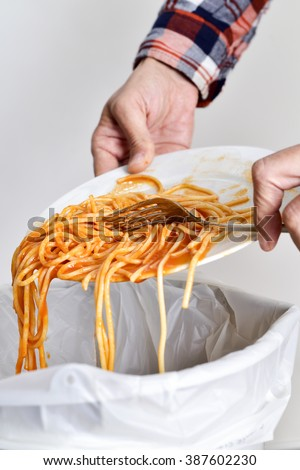 closeup of a young man throwing the leftover of a plate of spaghetti to the trash bin - stock photo