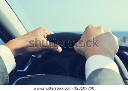 closeup of a young man wearing a gray suit driving a car, with a filter effect - stock photo