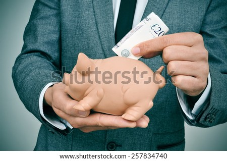 closeup of a young man wearing a suit introducing a pound sterling bill in a piggy bank - stock photo