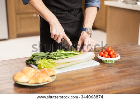 Closeup of a young man wearing an apron and chopping some vegetables to make a salad at home - stock photo