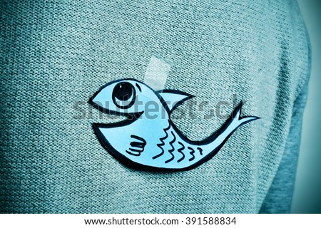 closeup of a young man with a paper fish attached with tape to his back, with a slight vignette added - stock photo