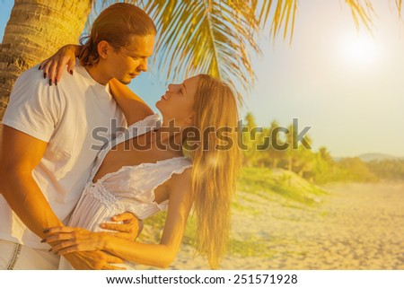 Closeup of a young romantic couple in embrace on an exotic beach - stock photo