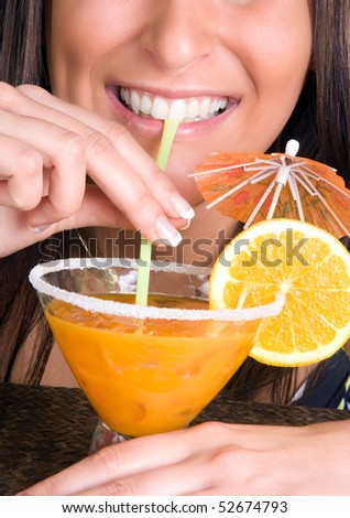 Closeup of a young woman drinking an orange cocktail