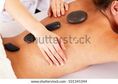 Closeup of a young woman getting spa treatment, focus on her back - stock photo