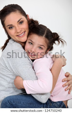 Closeup of a young woman hugging a little girl - stock photo