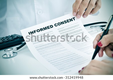 closeup of a young woman patient signing an informed consent at the doctors office - stock photo