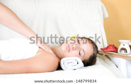 Closeup of a young woman relaxing during a massage at the spa - stock photo