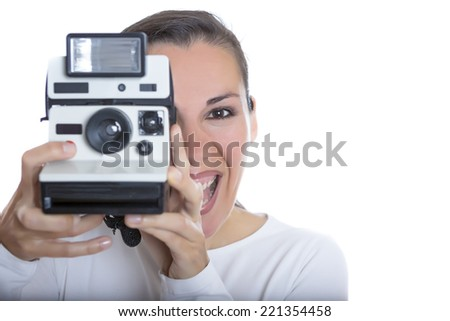 closeup of a young woman smiling holding an instant camera trying to take a picture isolated on a white backboard - focus on the face