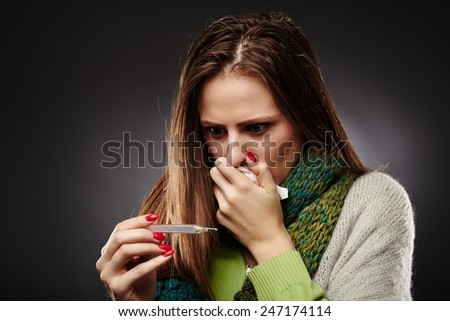 Closeup of a young woman with flu looking at the thermometer with worry - stock photo