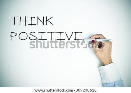 closeup of a young woman writing the sentence think positive with a pen on a white surface, slight vignette added - stock photo
