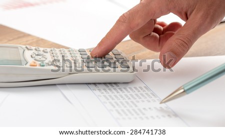 Closeup of accountant doing a calculation on a white calculator. - stock photo