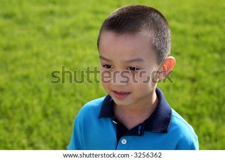 closeup of adorable asian boy in grass