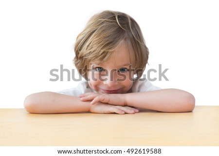 Closeup of adorable little boy on the table edge, smiling, head on crossed hands. Adorable child isolated on white