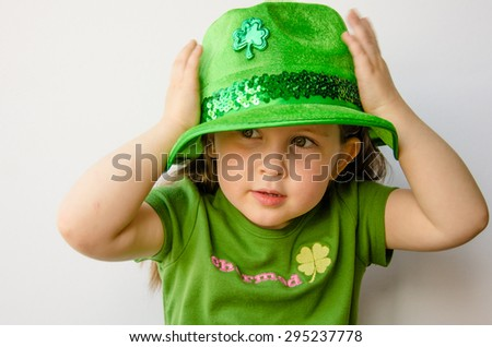 Closeup of adorable little girl with brunette hair trying on a green hat with a shamrock to celebrate St. Patrick's Day. - stock photo