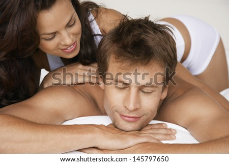 Closeup of affectionate young couple lying in bed - stock photo