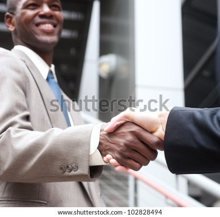 closeup of African American businessman shaking hands with caucasian businessman - stock photo