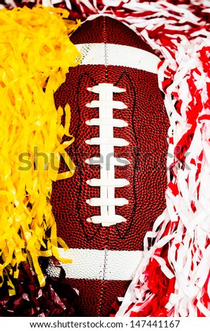 Closeup of American football and pom poms.