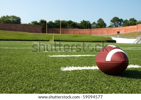 Closeup of American football on field with goal post in background - stock photo