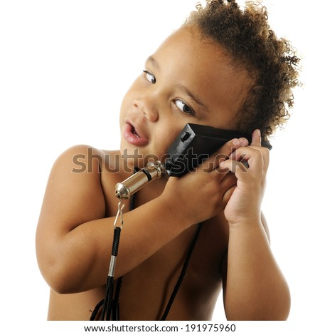 Closeup of an adorable, bare-chested preschooler pretending to talk on a plastic toy phone, though its not a phone.  On a white background.