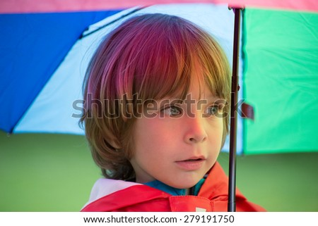 Closeup of an adorable little boy with rainbow colors umbrella in the rain