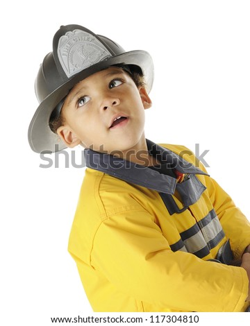 Closeup of an adorable preschool fireman in full gear looking up and back.  On a white background. - stock photo