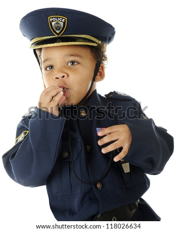 Closeup of an adorable preschool policeman blowing his whistle.  On a white background.