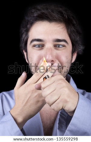 Closeup of an adult man (30 years old), which  appears to be quite a bum, looking extremely delighted as he is about to start smoking a marijuana spliff. Isolated on black background. - stock photo