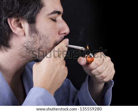 Closeup of an adult man (30 years old) with his profile to the camera. He appears to be quite a bum, concentrated in lighting a marijuana spliff (aka reefer; joint). Isolated on black background. - stock photo