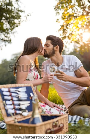 Closeup of an affectionate young couple kissing and having champagne outdoors. - stock photo