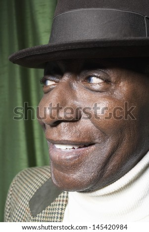 Closeup of an African American senior man wearing a hat against green curtain - stock photo