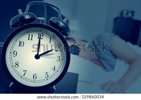 closeup of an alarm clock on a nightstand adjusting backward one hour at the end of the summer time, while a young man sleeps in bed - stock photo