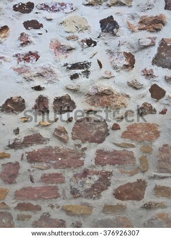 Closeup of an ancient irregular bricks wall with varicouloured elements