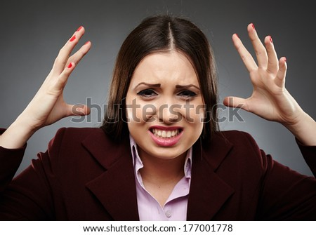 Closeup of an angry stressed businesswoman over gray background