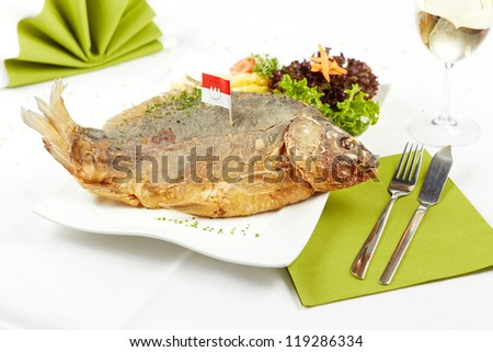 closeup of an appetizing carp with potato salad - stock photo