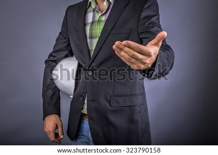 Closeup of an  architect man holding white hardhat under his arm while welcoming someone isolated over gray background - stock photo