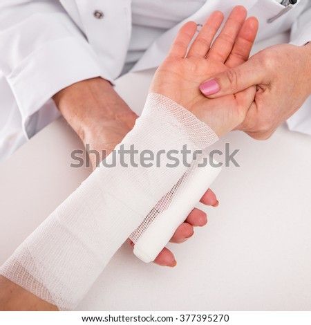 closeup of an arm, nurse is bandaging