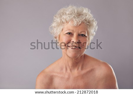 Closeup of an attractive old lady with a sweet smile on her face. Senior woman smiling on grey background. - stock photo