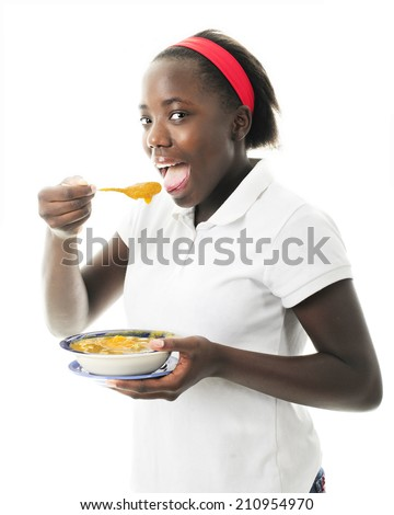 Closeup of an attractive tween enjoying pumpkin soup in celebration of Haitian Independence Day, January 1.  On a white background. - stock photo