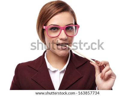 Closeup of an attractive young teacher holding a pen in the mouth, wearing nerd glasses and having a sexy attitude, isolated on white - stock photo