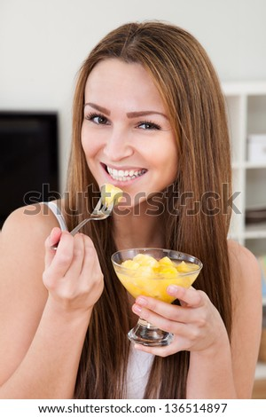 Closeup Of An Attractive Young Woman Eating Fruit Salad