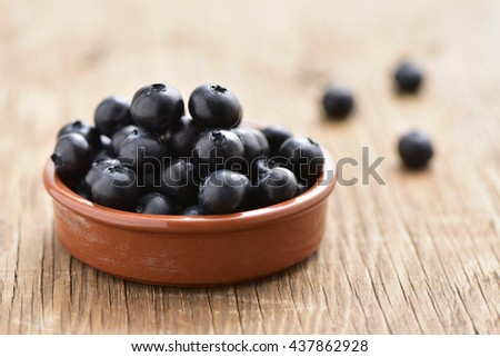 closeup of an earthenware bowl with some appetizing ripe blueberries, on a rustic wooden table - stock photo