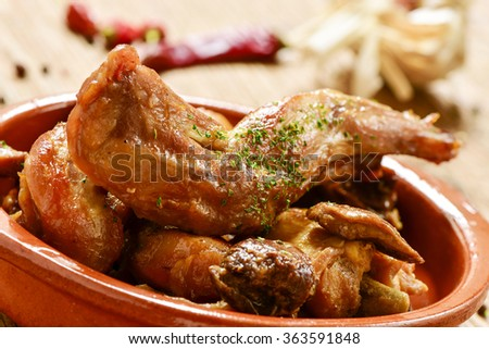 closeup of an earthenware with conejo al ajillo, a typical spanish recipe of rabbit with garlic an parsley, on a rustic wooden table