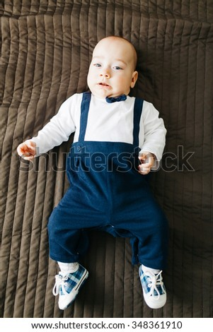 Closeup of an elegant baby boy lying in bed and looking at camera - stock photo
