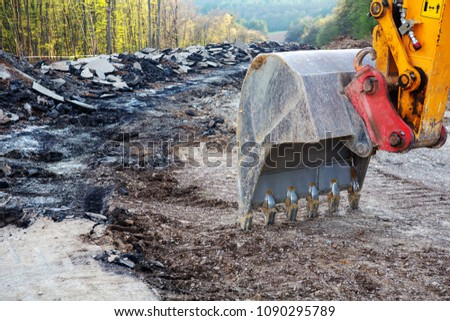 closeup of an excavator shovel digging in dirt at road construction