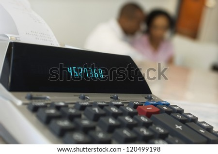 Closeup of an expense receipt machine with couple in the background - stock photo