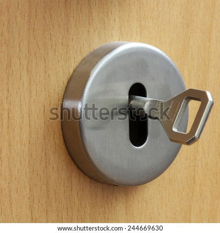 Closeup of an  keyhole with key on a wooden  door - stock photo
